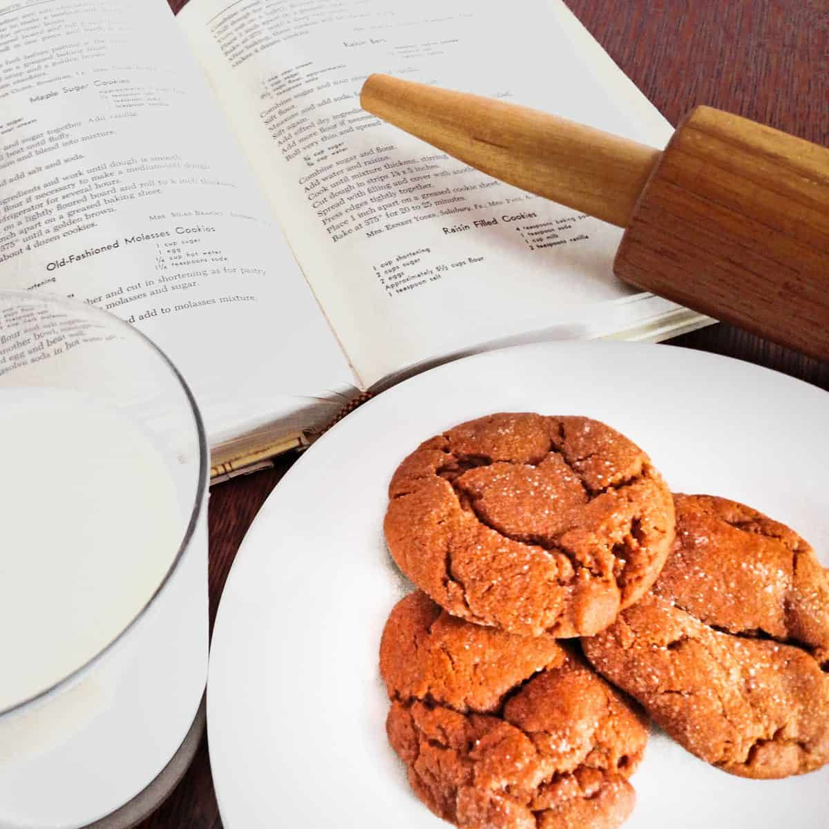 Plate of molasses cookies with a rolling pin, a glas of milk and the Mennonite Community Cookbook.