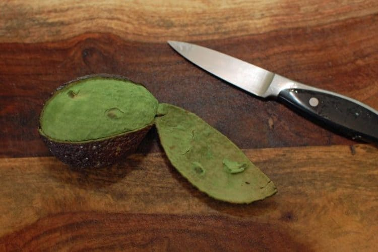 A knife sitting on top of a wooden cutting board, with Avocado