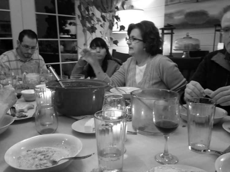 A group of people sitting at a table at home