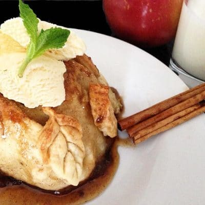 Apple dumpling with ice cream on top with two cinnamon sticks on the side.