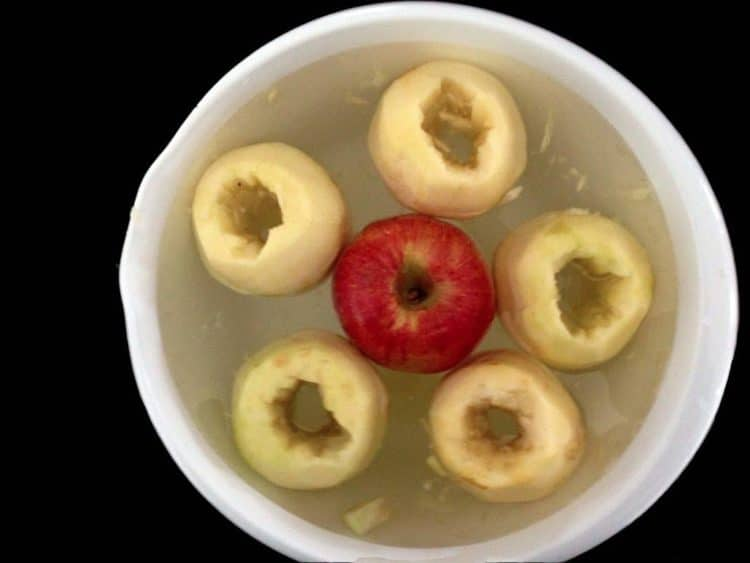 Cored apples sitting in a bowl of water.