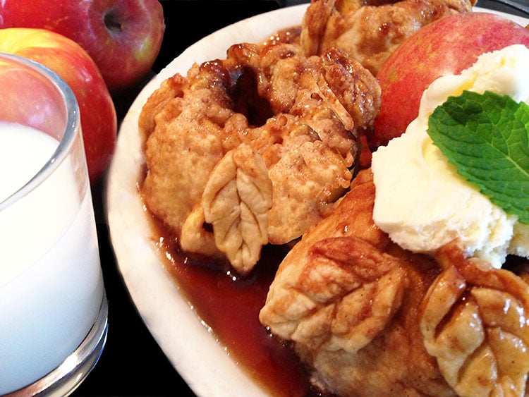 Plate of apple dumplings topped with vanilla ice cream and a glass of milk on the side.