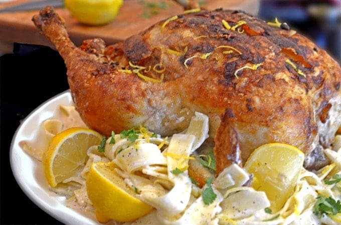 A whole roasted chicken with lemons and noodles