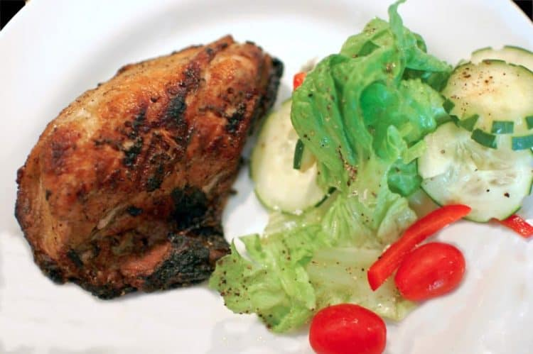 Plate of Cornell chicken with lettuce salad.