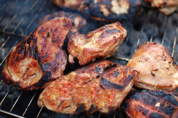 Several pieces of Cornell Chicken Barbecue on the grill.