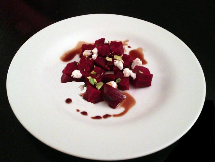 A plate of food on a table, with beet salad and goat cheese