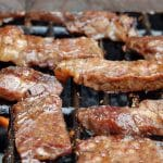 Strips of jerked beef on the grill.