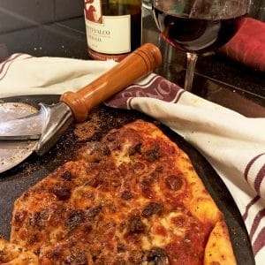 A pizza on a baking stone with a glass of red wine