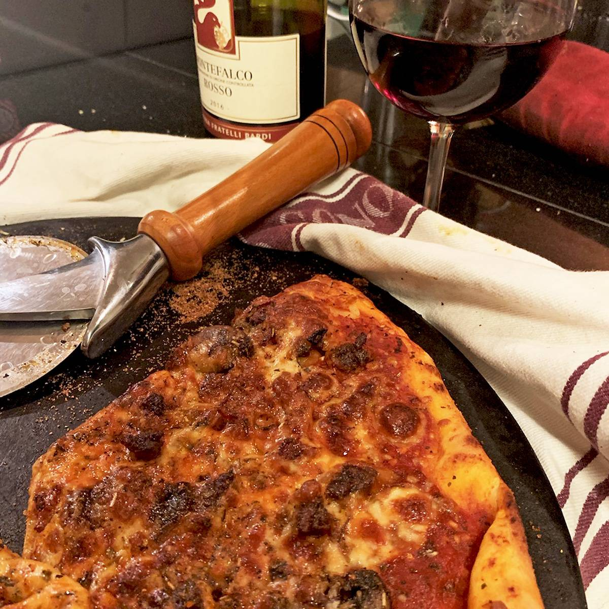 Homemade pizza on a pizza stone with glass of wine.