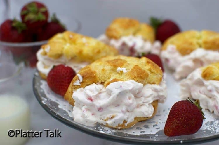 A platter of strawberry cream puffs with fresh strawberries