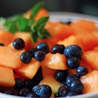 A bowl of fruit, with Cantaloupe and Berry