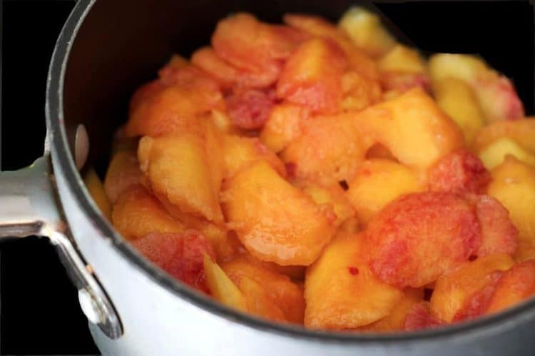A saucepan filled with peaches