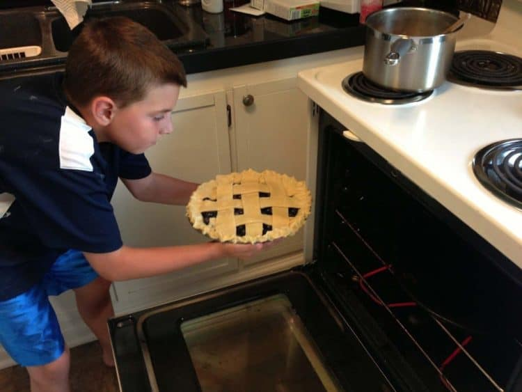 A boy putting a homemade pie in the oven