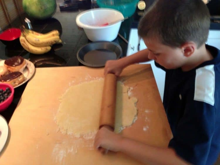 A young boy rolling out a pie crust