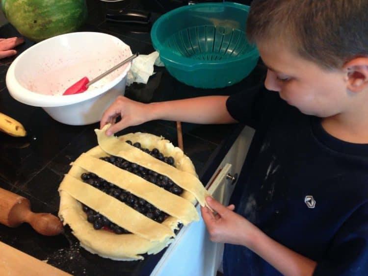A boy putting a lattice crust on a blueberry pie
