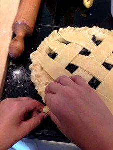 A pair of hands crimping a pie crust