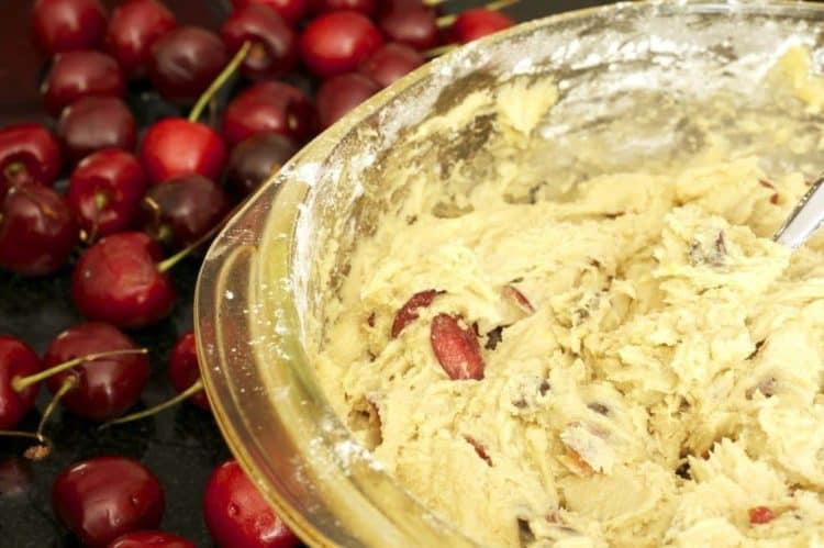 A bowl of cookie batter with bing cherries