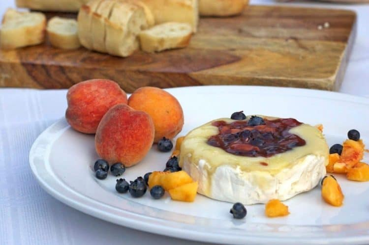 A plate of food on a table, with peaches and brie cheese