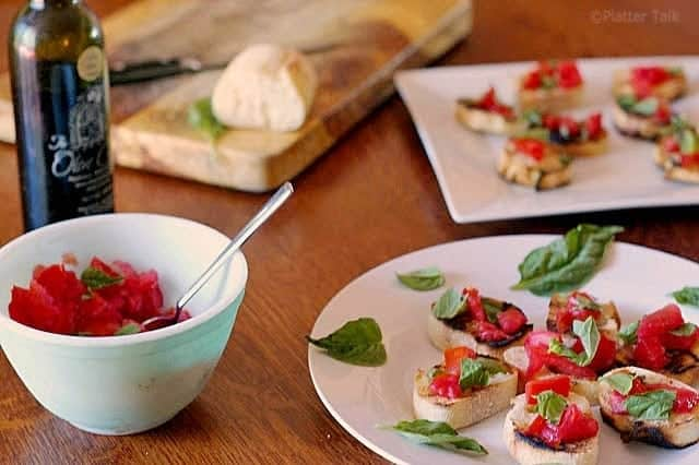 A bowl of food on a plate on a table, with Bruschetta and Tomato