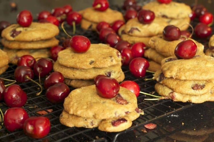 Stacks of cookies with cherries on a cooling rack
