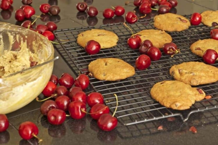 Cookies and bing cherries on a cooling rack