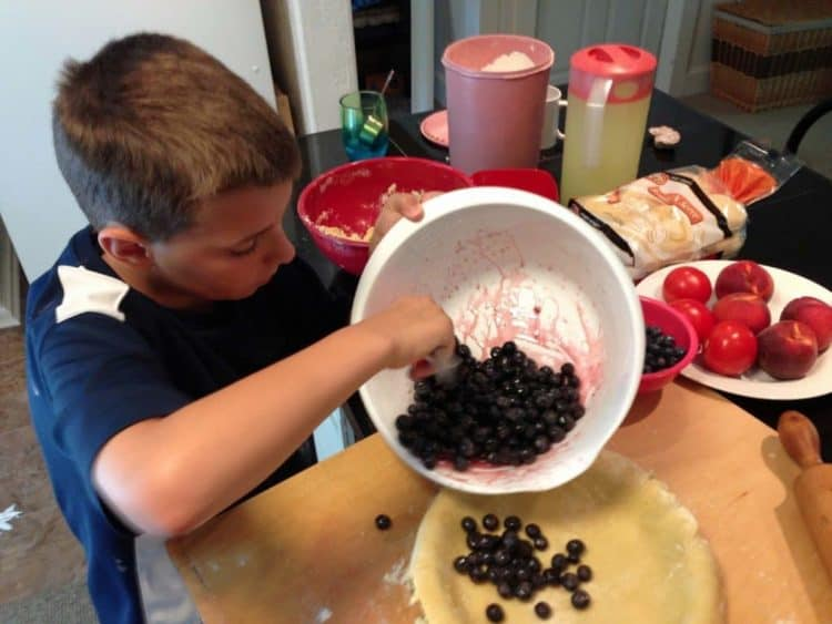 A young boy making a blueberry pie