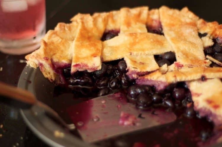 A close up of a plate of a cut blueberry pie