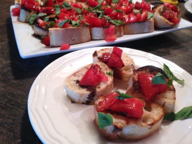 A plate of appetizers of bread and tomato.