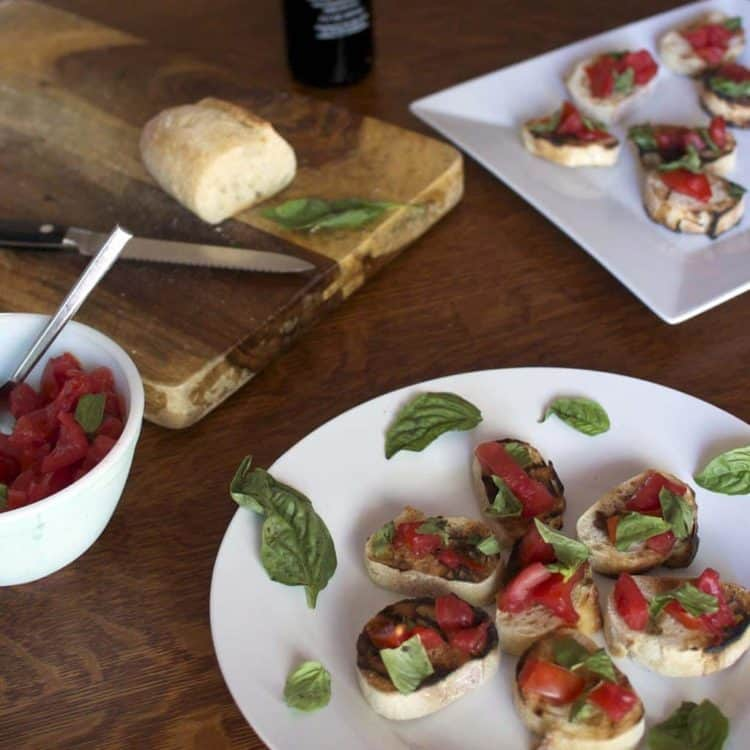 A plate of food on a table, with Bruschetta and Tomato