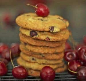 A stack of cookies with bing cherries