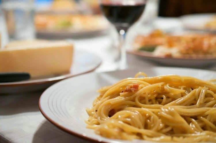 A plate of carbonara with a glass of wine.