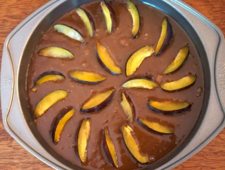 A pan full of cake batter and plums.