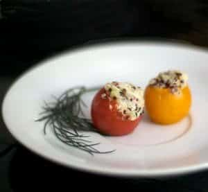 A plate of food with two stuffed tomatoes.