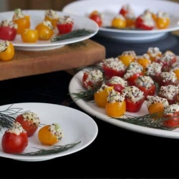 A table with plates of stuffed Cherry tomato.