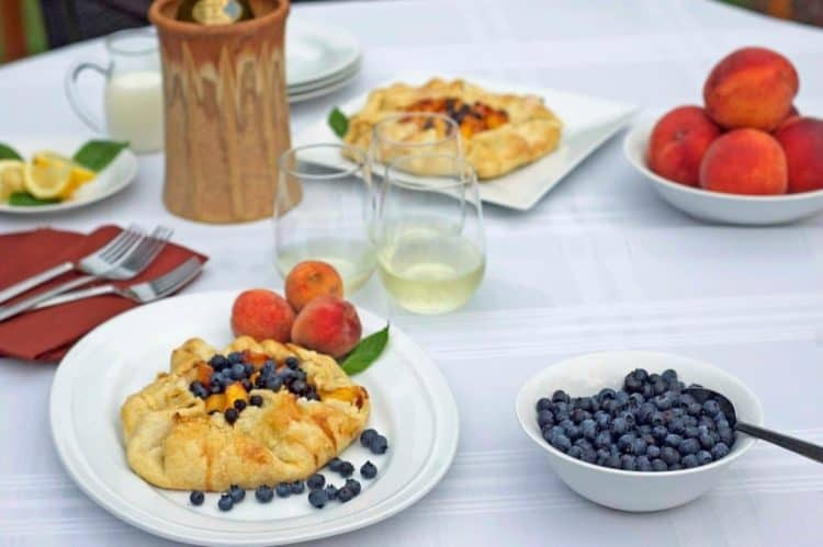 A table topped with plates of fruit tart.