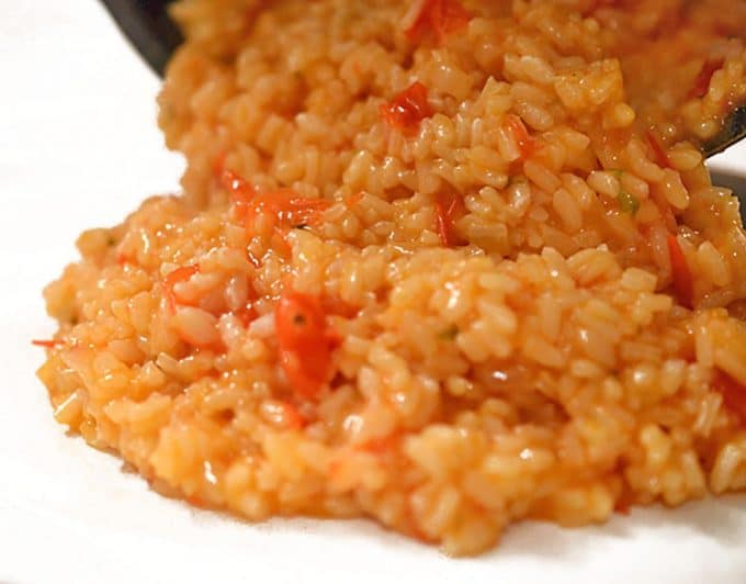 Risotto al pomodoro being served on a white plate.