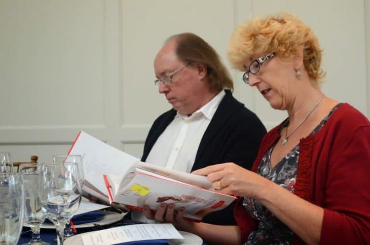 A man and a woman looking at a paper.