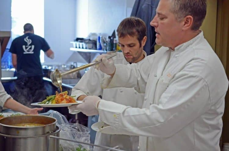 A group of people preparing food in a bowl, with Cook and Chef.