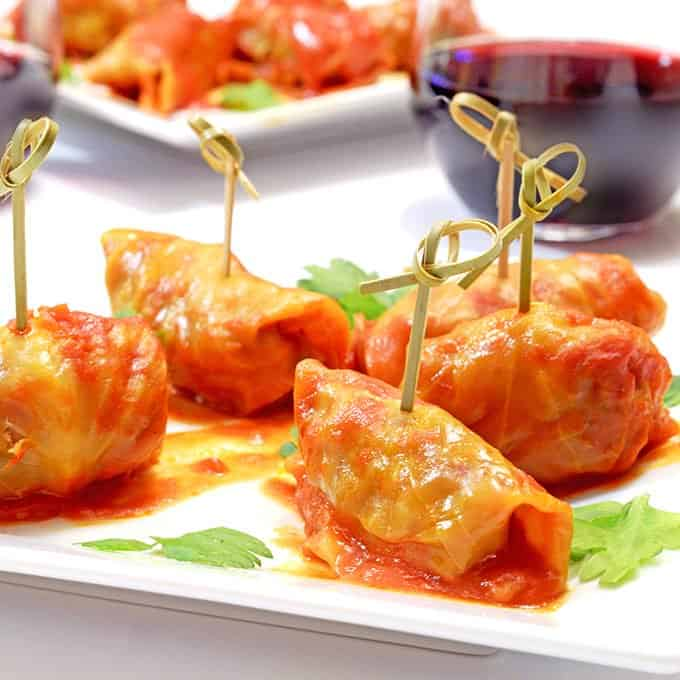 Mini stuffed cabbage with cocktail picks on garnished plate