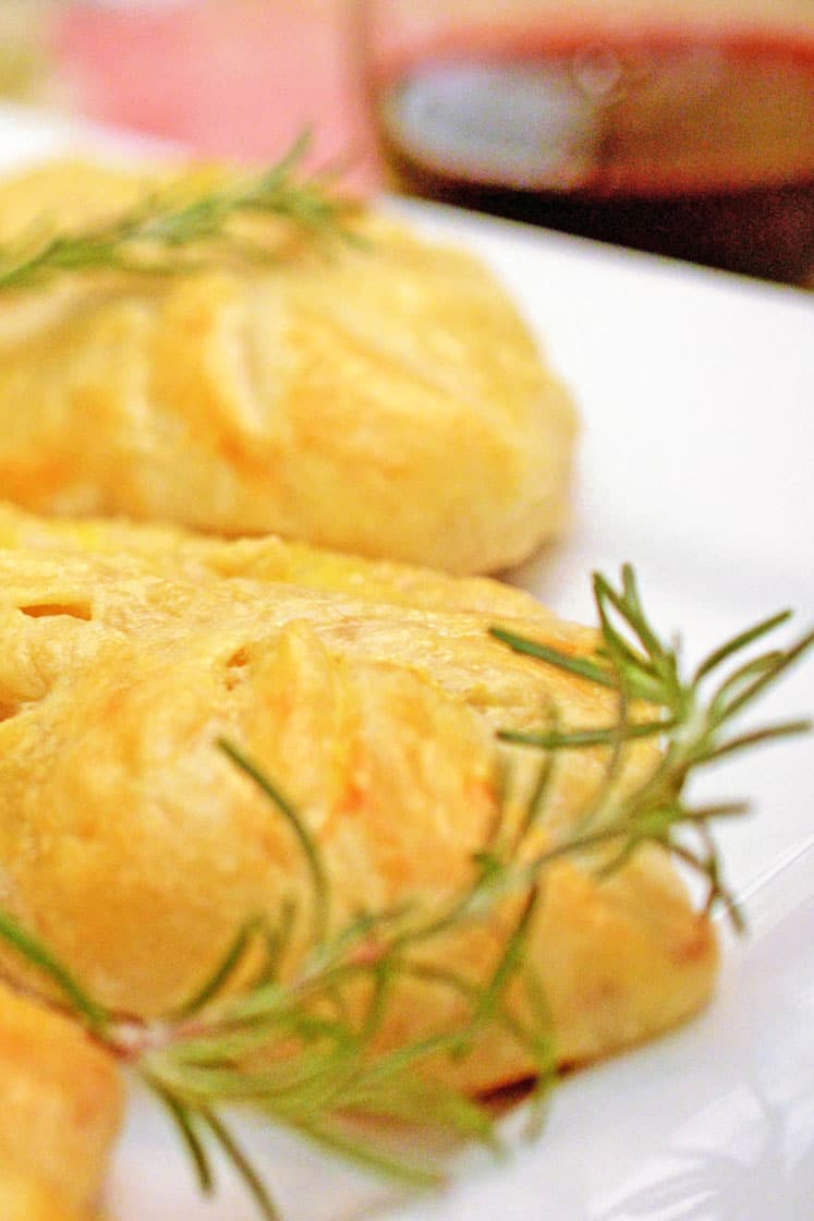 Serving of pork wellington garnished with fresh rosemary