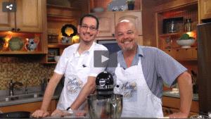 2 men standing behind a mixer, at a kitchen counter