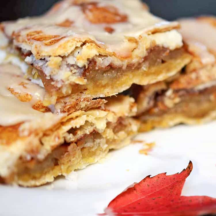 Cut glazed apple bars stacked on serving plate with fall leaf