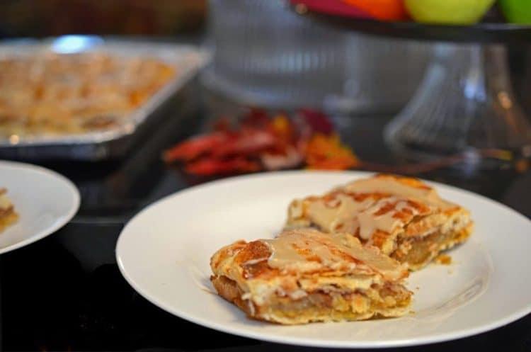 Angled servings of glazed apple dessert bar on plate, Autumn leaves in background