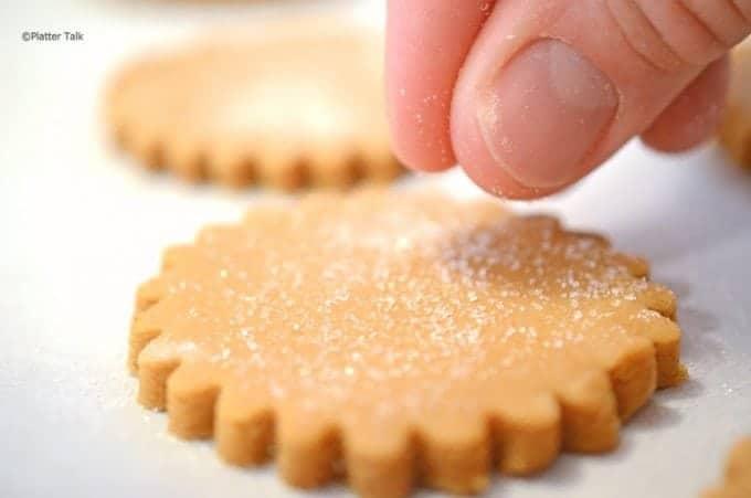 Sprinkling sugar on top of a Christmas cookie.