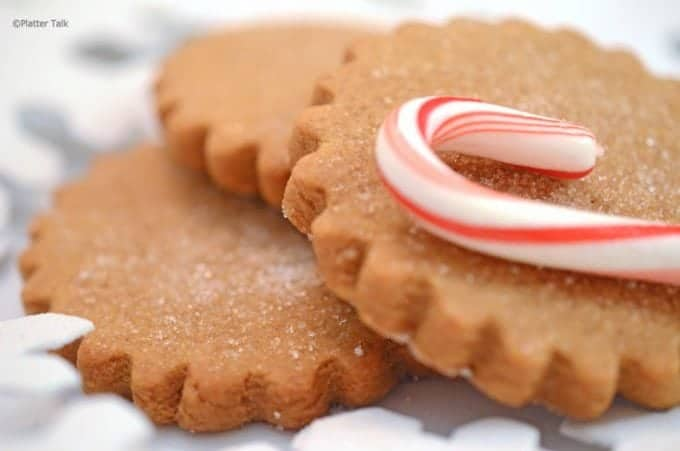 Three star-shaped gineger cookies with a candy cane.
