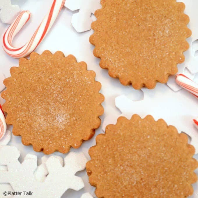 Overhead view of ginger cookies with snow flake cutouts and a candy cane.