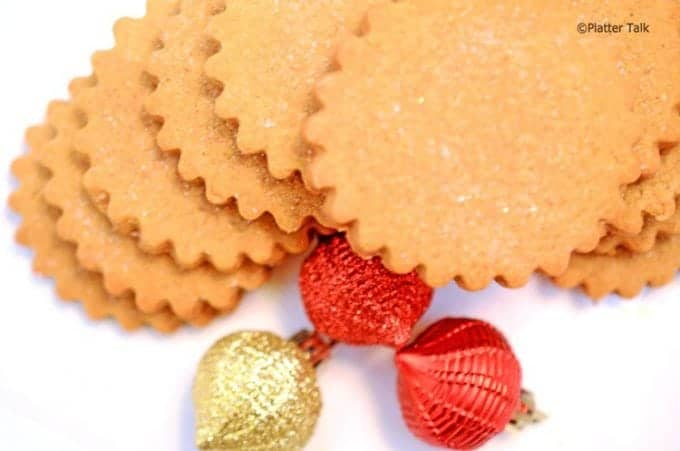 Stack of ginger cookies with Christmas ornaments.