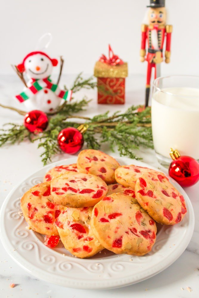 Plate of Cherry Christmas cookies with garland and a glassof milk.
