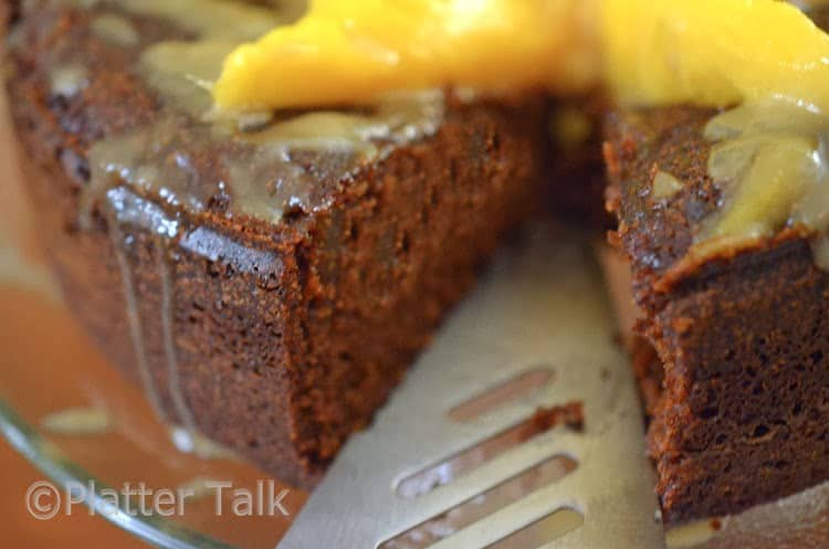 a ginger cake with mango and brandy glaze with a piece taken from it