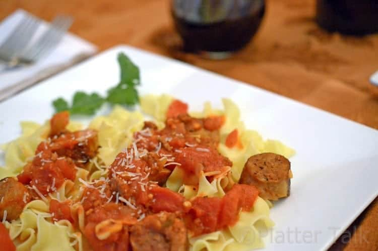 A plate of food on a table, with Sausage.